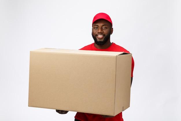 Service de livraison - bel homme de livraison afro-américain transportant une boîte d'emballage.