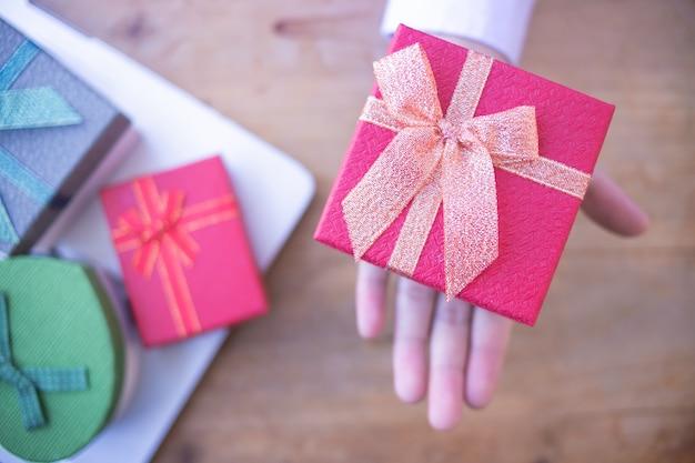 Service de livraison de bureau. photo recadrée d'homme d'affaires en chemise assis au bureau avec boîte-cadeau rouge.