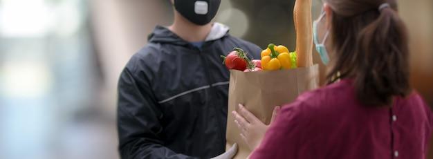 Service de livraison homme remettant le sac de nourriture fraîche à la clientèle féminine