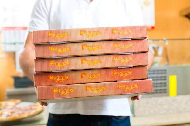 Service de livraison, homme tenant des boîtes à pizza