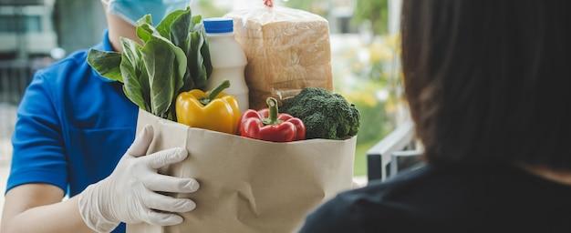 Service de livraison de nourriture homme portant un masque de protection remettant un sac de nourriture fraîche