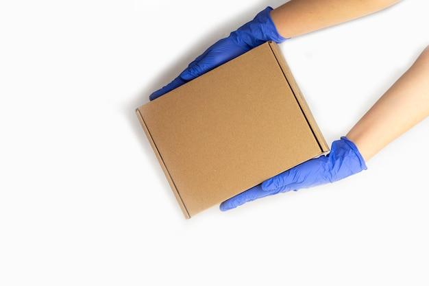 Service de livraison pendant la quarantaine. la main dans des gants en caoutchouc détient une boîte en carton. restez à la maison, faites des achats en ligne pendant une épidémie de coronavirus.