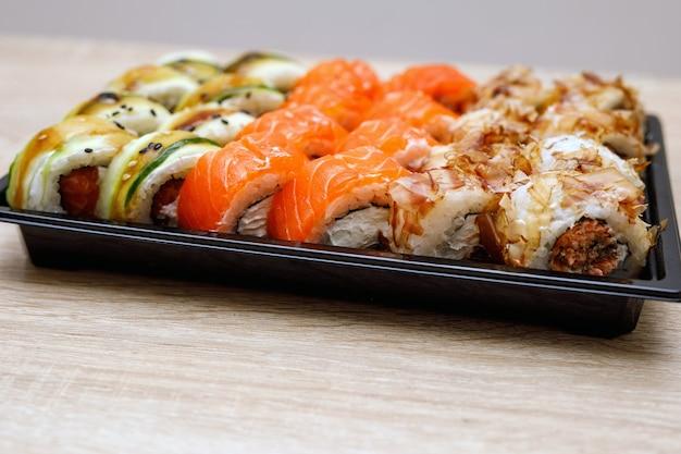 Service de livraison - rouleaux de sushi dans une boîte en plastique.