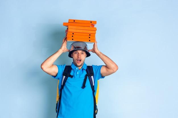 Service de livraison sans contact pendant la quarantaine. l'homme livre de la nourriture et des sacs à provisions pendant l'isolation. émotions de livreur isolé sur bleu