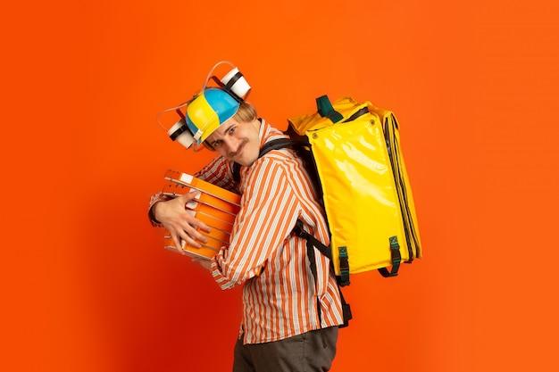 Service de livraison sans contact pendant la quarantaine. l'homme livre de la nourriture et des sacs à provisions pendant l'isolation. émotions de livreur isolé sur orange