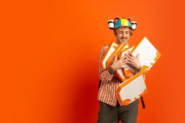 Service de livraison sans contact pendant la quarantaine. l'homme livre de la nourriture et des sacs à provisions pendant l'isolation. émotions de livreur isolés sur fond orange.