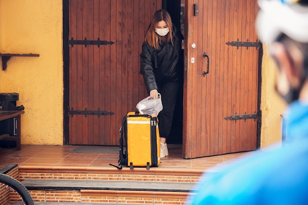 Service de livraison sans contact pendant la quarantaine. l'homme livre de la nourriture et des sacs à provisions pendant l'isolement. frapper à la porte et laisser les marchandises jusqu'à ce que le client les récupère. sécurité, réception, maintien à distance.