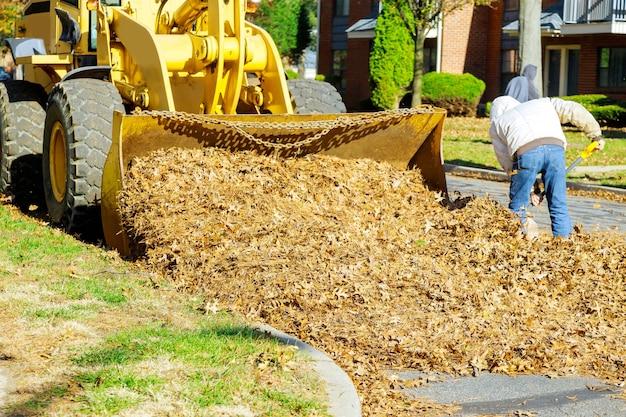 Le service municipal effectue des travaux d'automne dans les feuilles d'automne tombées avec une excavatrice