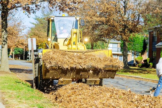 Le service municipal saisonnier travaille les lieux publics nettoie de la ville des feuilles tombées avec une excavatrice