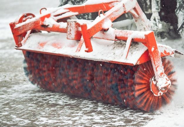 Service de nettoyage de la ville de la neige, un petit tracteur avec une brosse rotative efface une route dans le parc de la ville