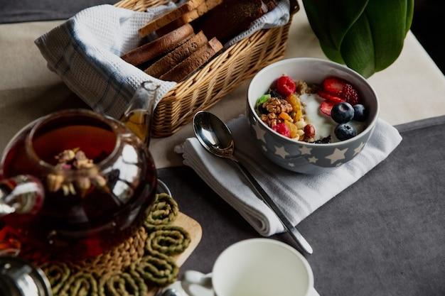 Service petit-déjeuner, flocons d'avoine aux baies et yaourt, thé noir aux roses, pain