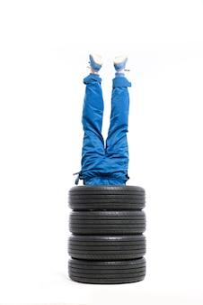 Service de pneus, les jambes du travailleur sortent de la pile de pneus, blanc, réparateur, montage de roue