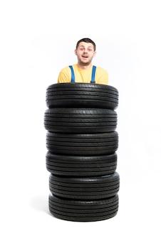 Service de pneus, travailleur est debout à l'intérieur d'un tas de pneus, blanc, réparateur, montage de roue