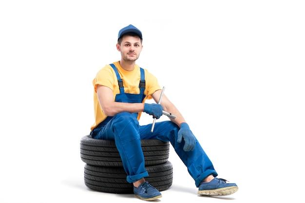 Service de pneus de voiture, travailleur en uniforme bleu assis sur des pneus de voiture, blanc, réparateur, montage de roue