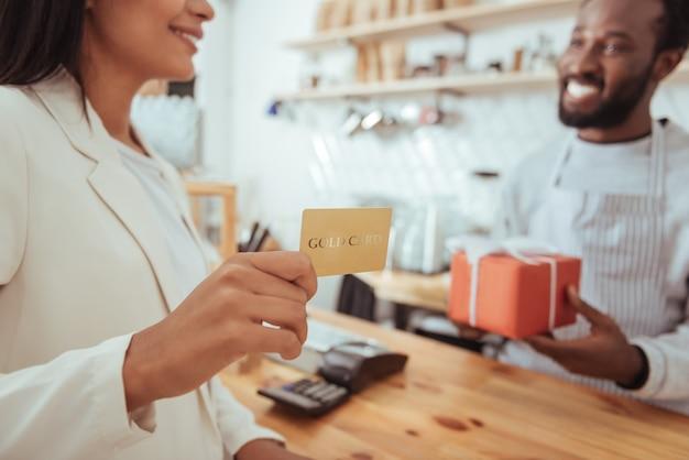 Service de qualité. l'accent étant mis sur les mains d'une belle jeune femme tenant une carte en or et étant prêt à payer sa commande dans le café