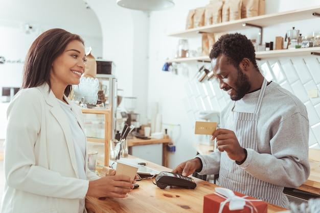 Service rapide. beau barista agréable tenant la carte de crédit de ses clients et effectuant une procédure de paiement tandis que le client tenant une tasse de café et attendant sa carte