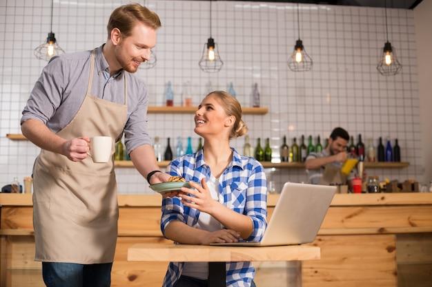 Service rapide. ravi positif gentil serveur souriant et regardant son client tout en servant sa nourriture