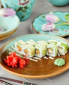 Service à sushi avec riz et sauce verte
