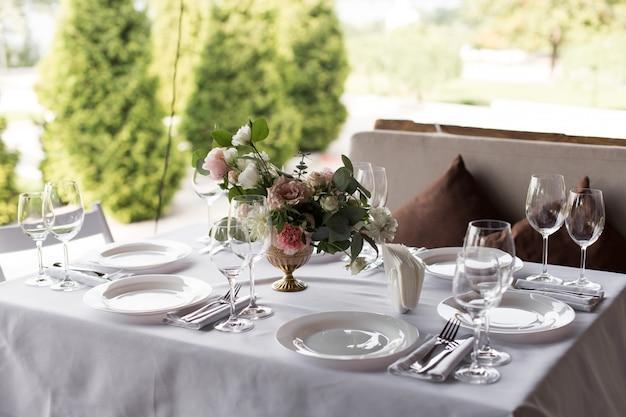 Service de table de mariage décoré de fleurs fraîches dans un vase en laiton. fleuristerie de mariage. table de banquet pour les invités à l'extérieur avec vue sur la nature verdoyante. bouquet de roses, d'eustoma et de feuilles d'eucalyptus.