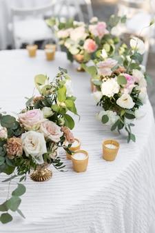 Service de table de mariage décoré de fleurs fraîches dans un vase en laiton. fleuristerie de mariage