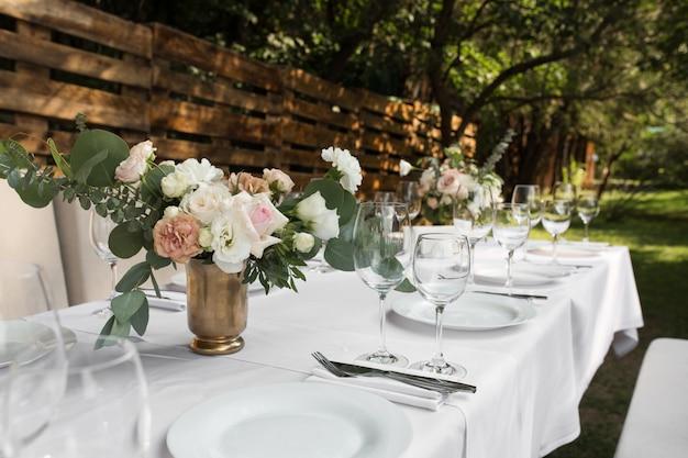 Service de table de mariage décoré de fleurs fraîches dans un vase en laiton