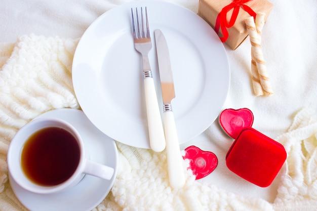 Service de table saint valentin avec boîte à bagues en velours rouge, bougies et argenterie