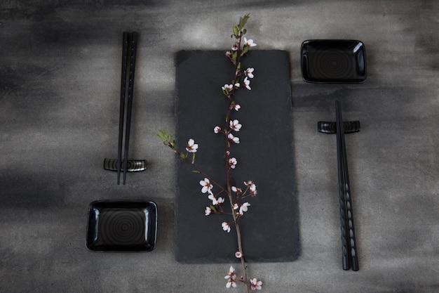 Service de table de style japonais: bâtons de sushi, assiettes et une branche de cerisier en fleurs