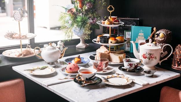 Service à thé anglais comprenant thé chaud, pâtisseries, scones, sandwichs et mini-tartes.