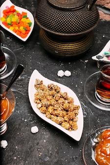 Service à thé avec beaucoup de confiture de gelée de couleur sucrée, bonbons susam, citron, confiture de pêche