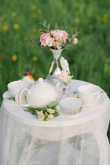 Un service à thé, un délicat bouquet de roses et d'eustoma dans un vase en argent sur une table basse avec une nappe en dentelle. décor de mariage, décor pour une soirée romantique