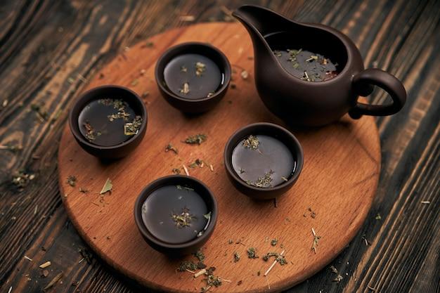 Service à thé et feuilles de thé sur fond de bois