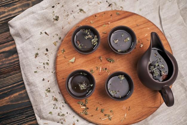 Service à thé et feuilles de thé vert sur une planche en bois
