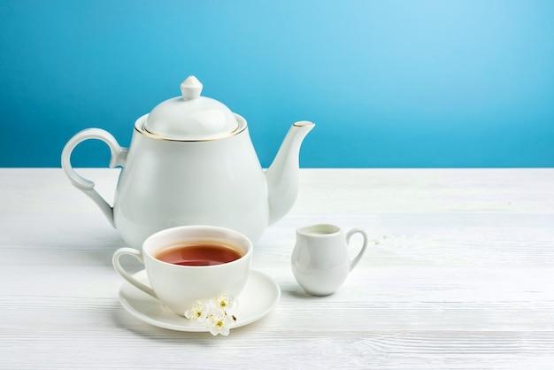 Service à thé sur fond bleu avec espace de copie. une tasse de thé, une théière et un pot à lait sur une table blanche.