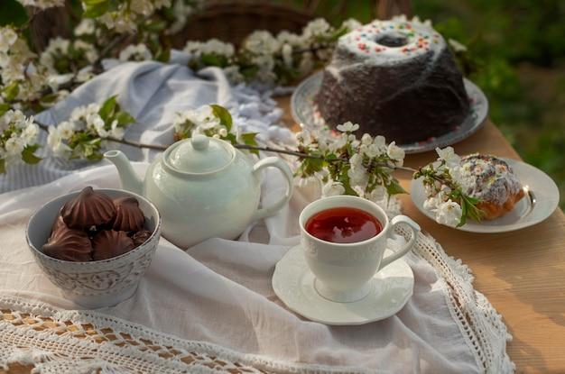 Service à thé sur une nappe blanche par une journée ensoleillée branches de fleurs de cerisier