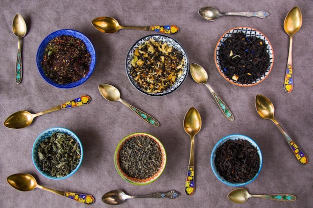 Service à thé sec à base de plantes et naturel, variation et collection de thé et cuillères vintage, high angle view