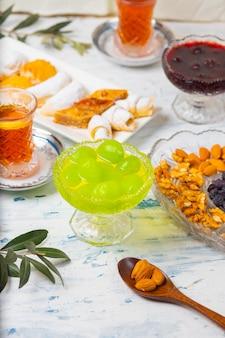 Service à thé avec des variétés de noix traditionnelles, citron, confiture et bonbons servis sur une nappe blanche