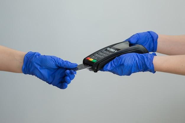 Services bancaires de monnaie électronique. succès financier et sécurité. machine à carte de crédit pour transaction d'argent. main de femme dans des gants avec carte de crédit glisser à travers le terminal pos et entrez le code pin.