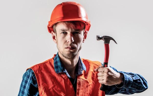 Services de bricoleur. industrie, technologie, homme constructeur, concept. travailleur de l'homme, casque de construction, casque. marteau martelant. constructeur dans le casque, constructeurs de bricoleur de marteau dans le casque