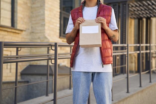 Services de courrier postal recadrée d'un courrier masculin tenant un petit sac en papier avec copie