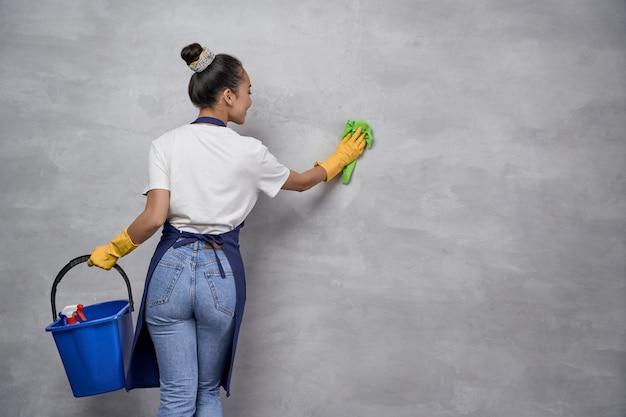 Services d'entretien ménager et de nettoyage. vue arrière de l'uniforme de la femme au foyer ou de la femme de chambre et des gants en caoutchouc jaune tenant un seau ou un panier avec différents produits de nettoyage et nettoyant un mur. désinfection