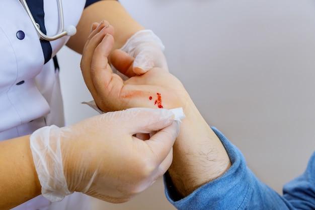 Services médicaux pour lingettes pansements médecin sur la main blessée