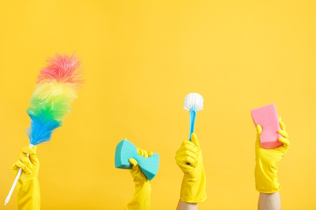 Services de ménage et de nettoyage. mains dans des gants en caoutchouc tenant des fournitures de nettoyage
