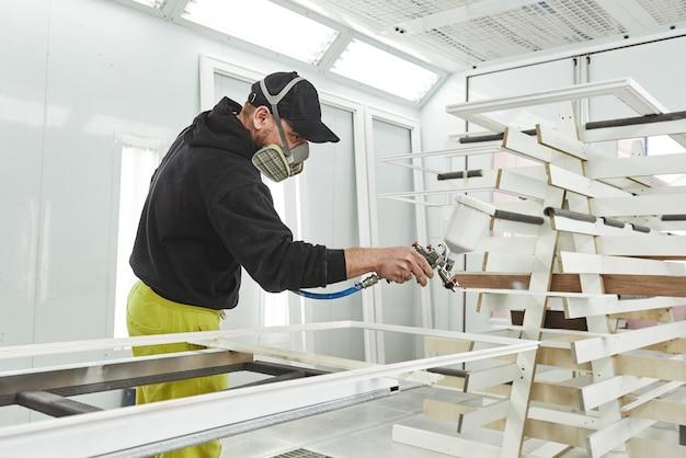 Services de peinture exceptionnels homme au masque respiratoire peignant des planches de bois à l'atelier