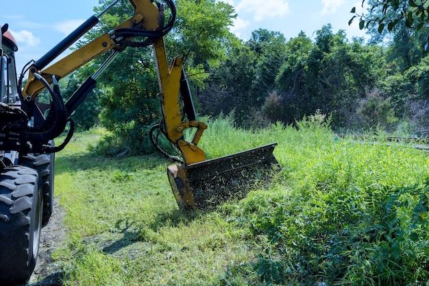 Les services routiers d'un tracteur avec tondeuse à gazon tondant la pelouse le long de la route sont des travaux d'aménagement paysager de machines