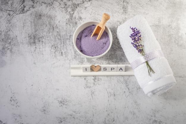 Serviette de bain torsadée avec sel de bain et lettres en bois épelant i love spa.