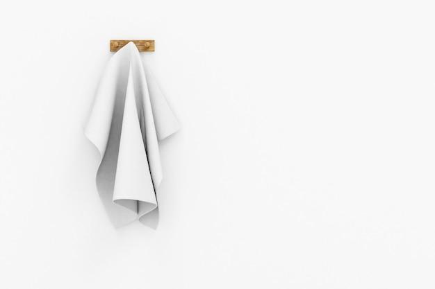 Serviette blanche accrochée à un crochet au mur blanc