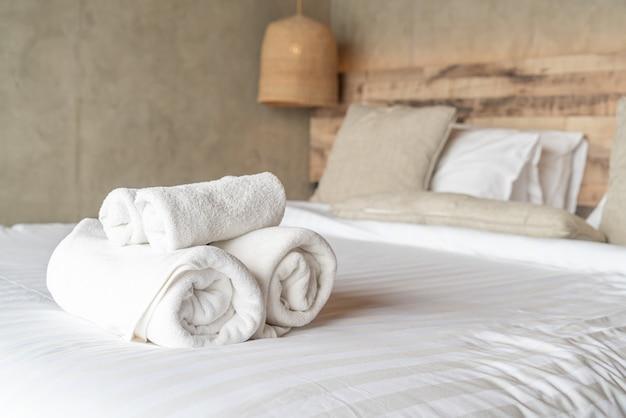 Serviette blanche sur la décoration du lit dans la chambre