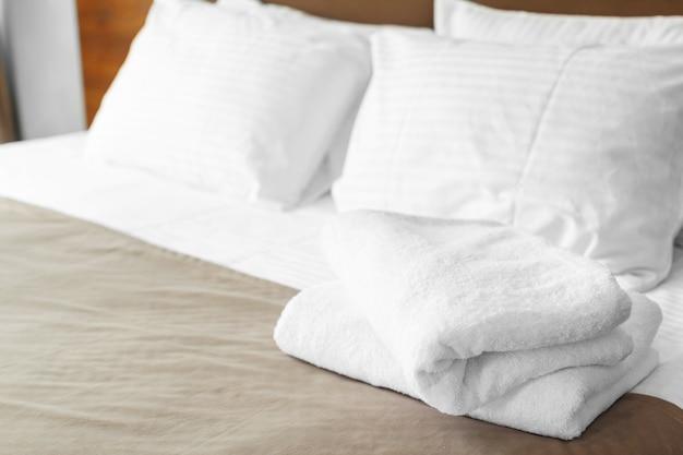 Serviette blanche sur le lit dans la chambre pour le client de l'hôtel