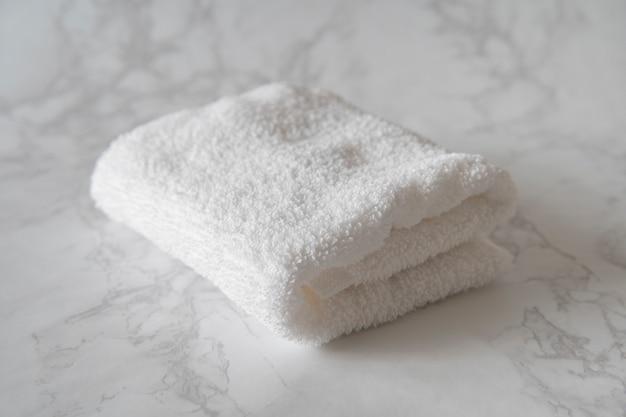 Serviette blanche placée sur une table en marbre blanc