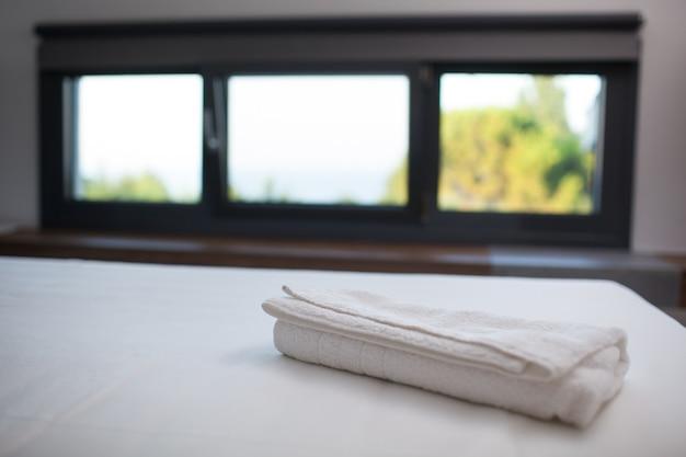 Serviette blanche propre sur le lit dans la chambre d'hôtel